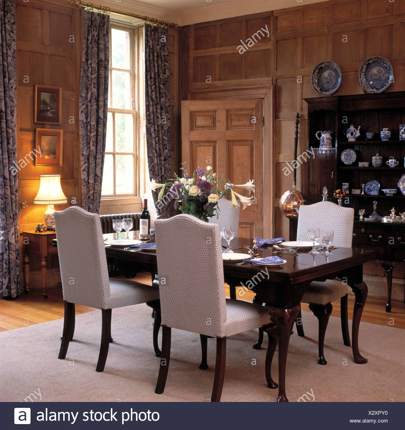 Upholstered Beige Highback Chairs And Antique Table In Panelled Country  Dining Room With Lighted Lamp On