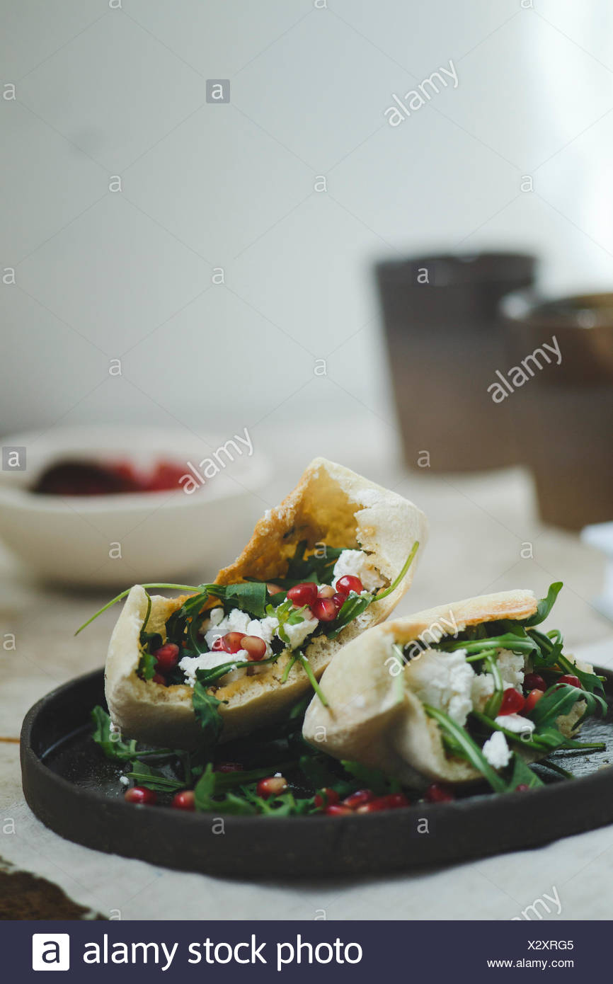 Sandwich in pita bread served on dark brown handmade ceramic plate - Stock Image