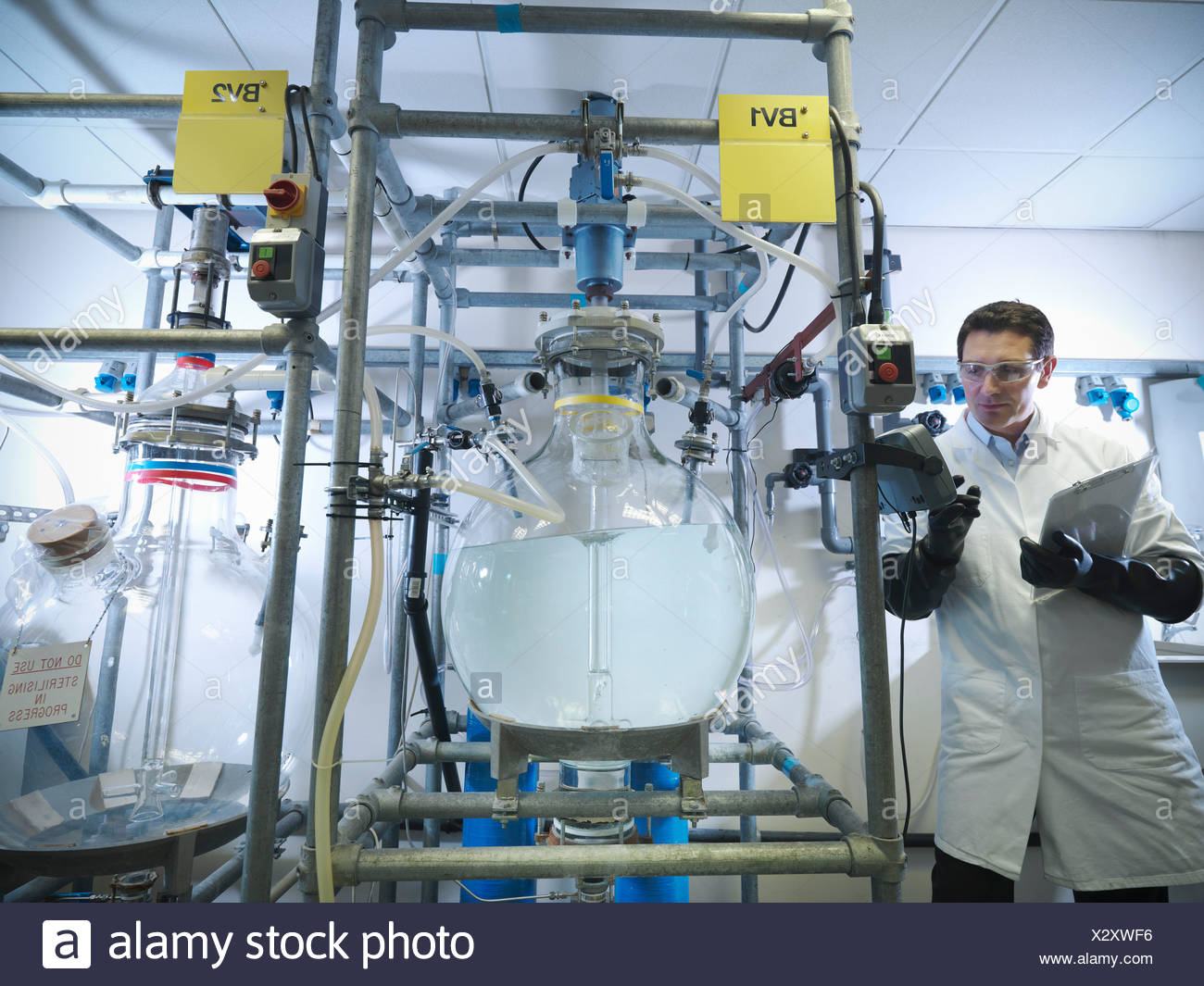 Scientist with laboratory mixing vessels - Stock Image