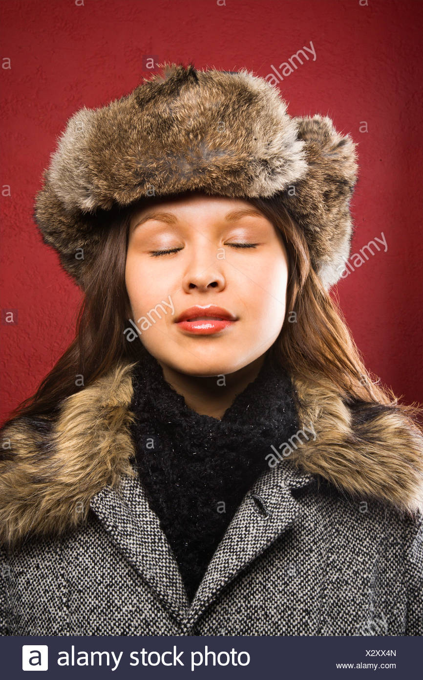 7365166773d Young adult Caucasian woman wearing fur hat with eyes closed - Stock Image
