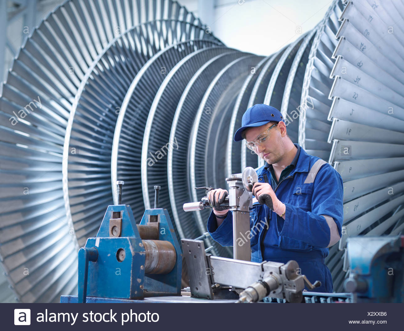 Engineer at workstation in front of steam turbine - Stock Image