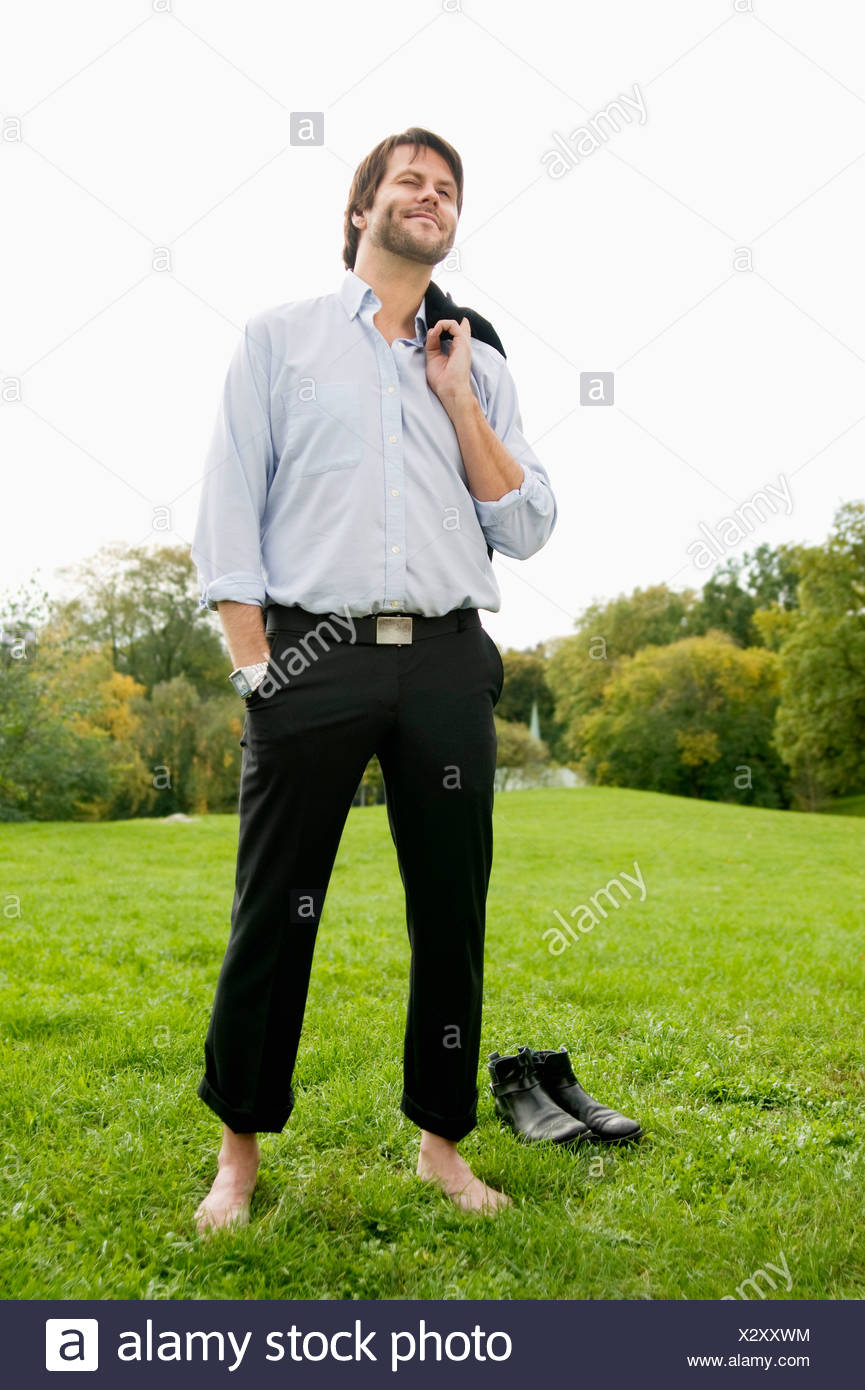 Man standing bare foot on lawn - Stock Image