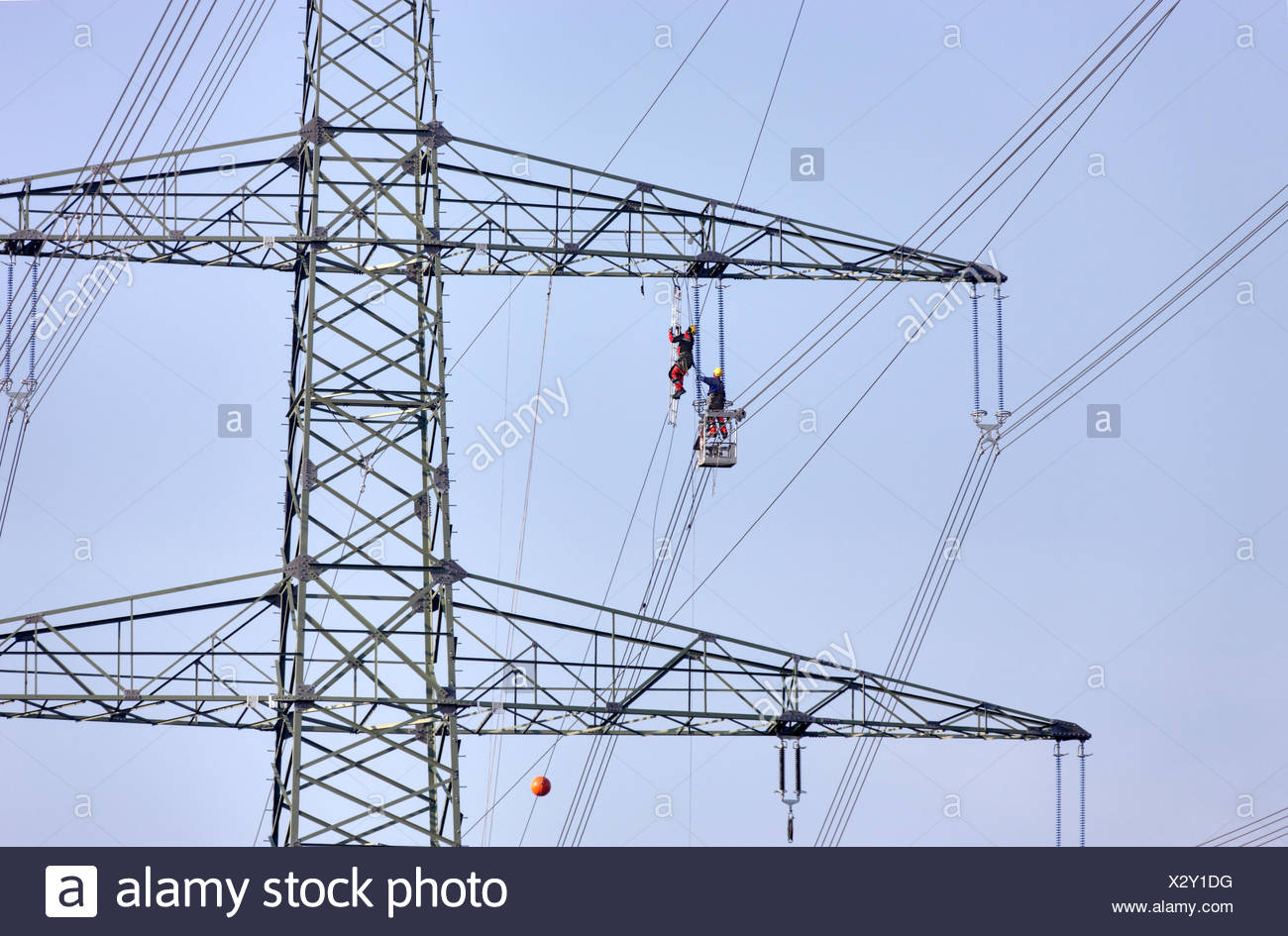 High-voltage pole, power line wire installation, man climbing to side arm, other man supporting him from a gondola, Thuringian Forest - Stock Image