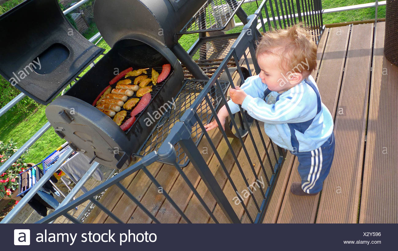 little boy curiously grabbing through a fence on a veranda in front of a grill full of meat and sausages - Stock Image