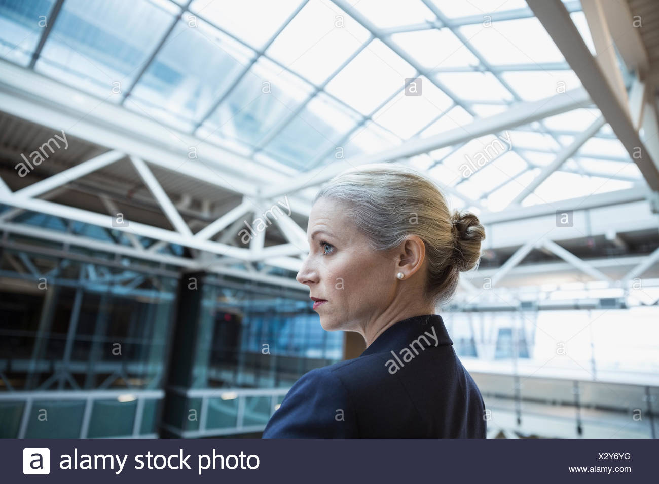 Serious businesswoman in atrium - Stock Image