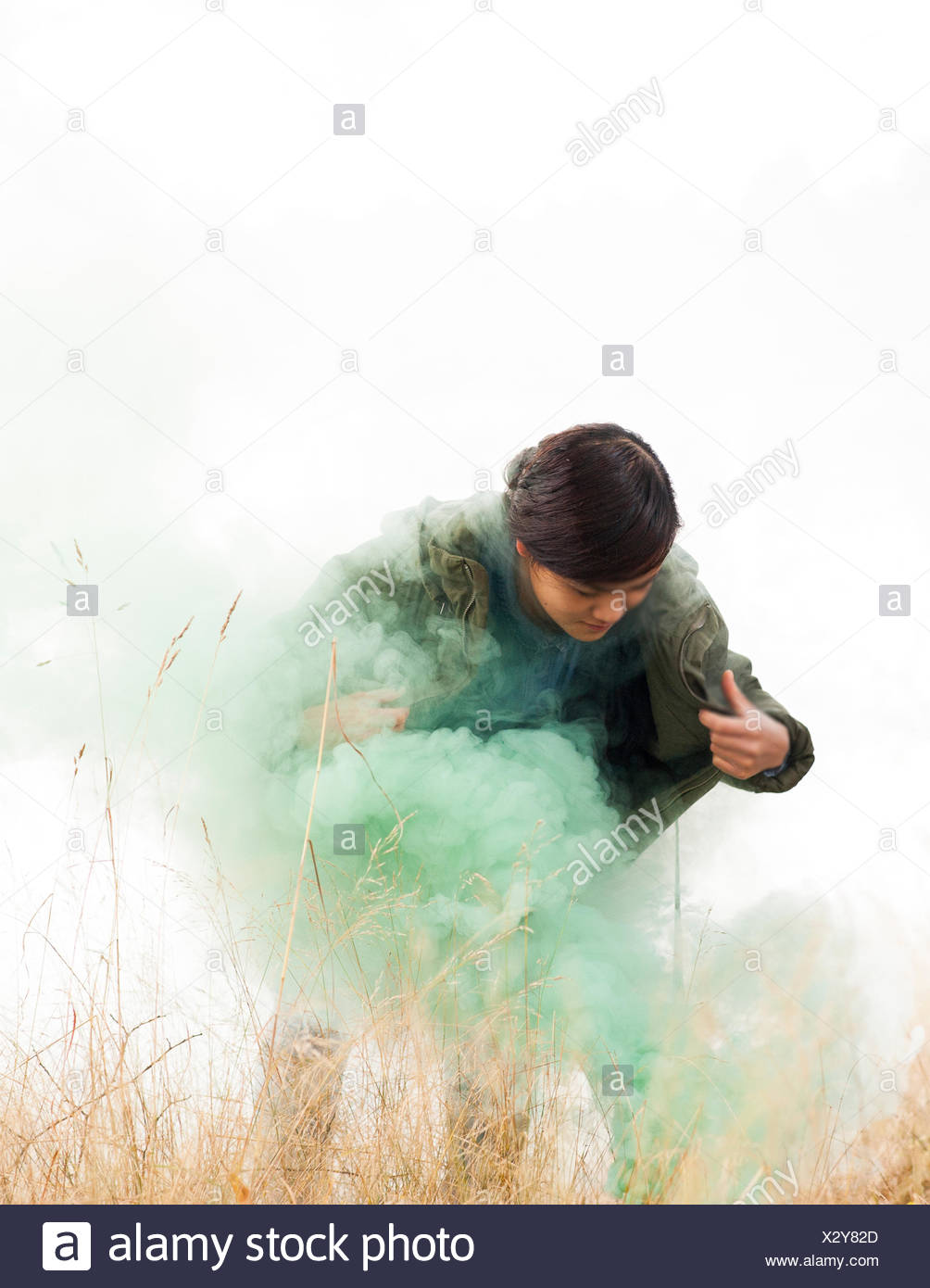 Norway, Woman standing in grass and green smoke - Stock Image