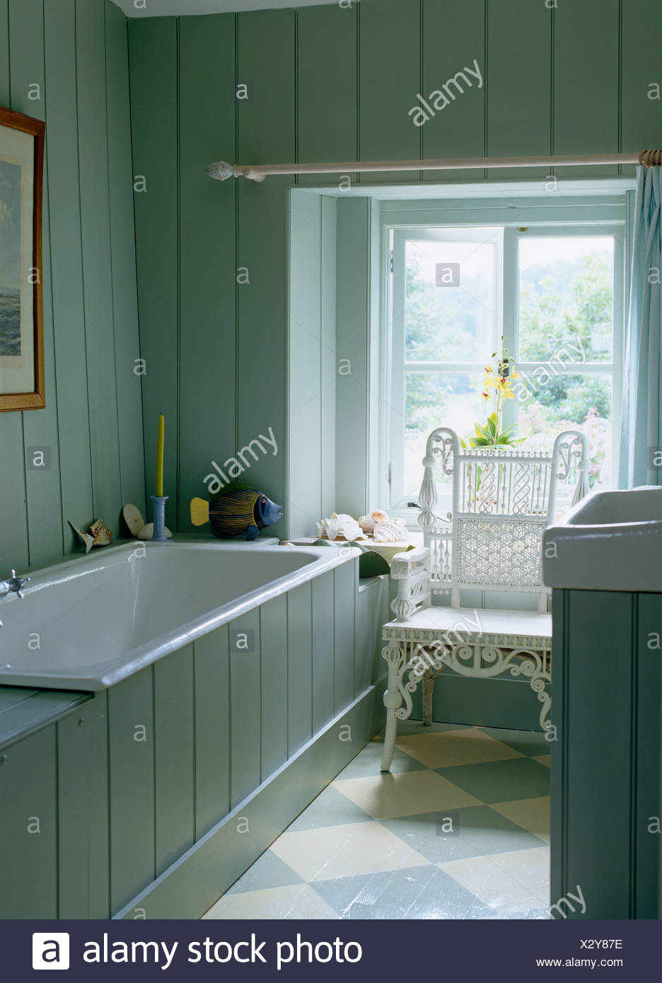 White wicker chair and painted floor in country bathroom with pale ...
