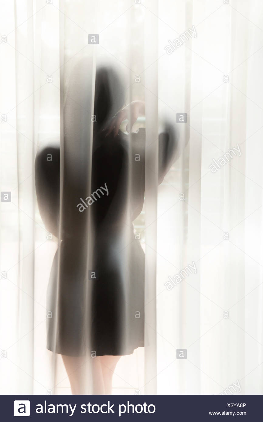 Woman behind curtain looking through window - Stock Image