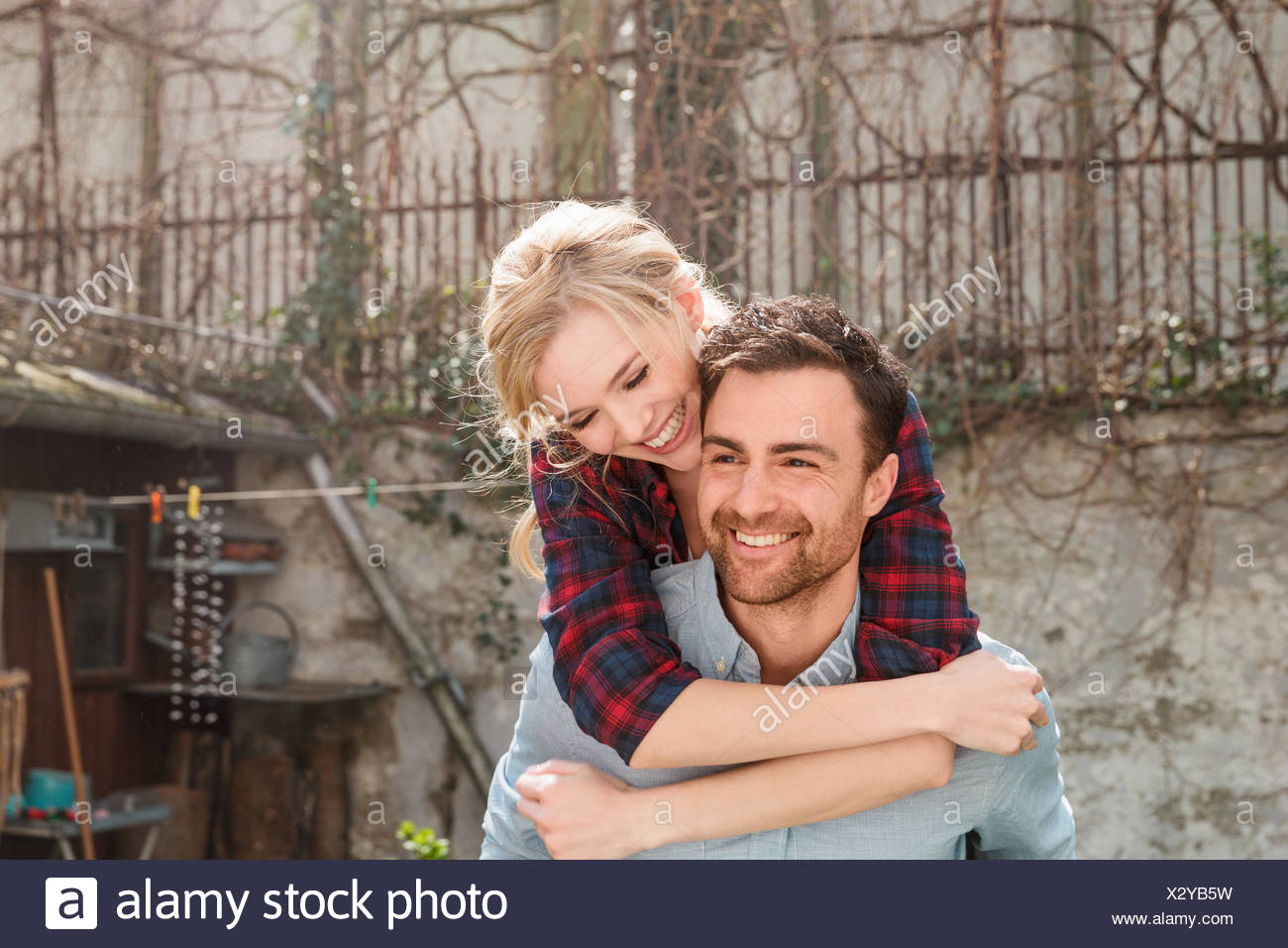 Man giving woman piggyback smiling - Stock Image