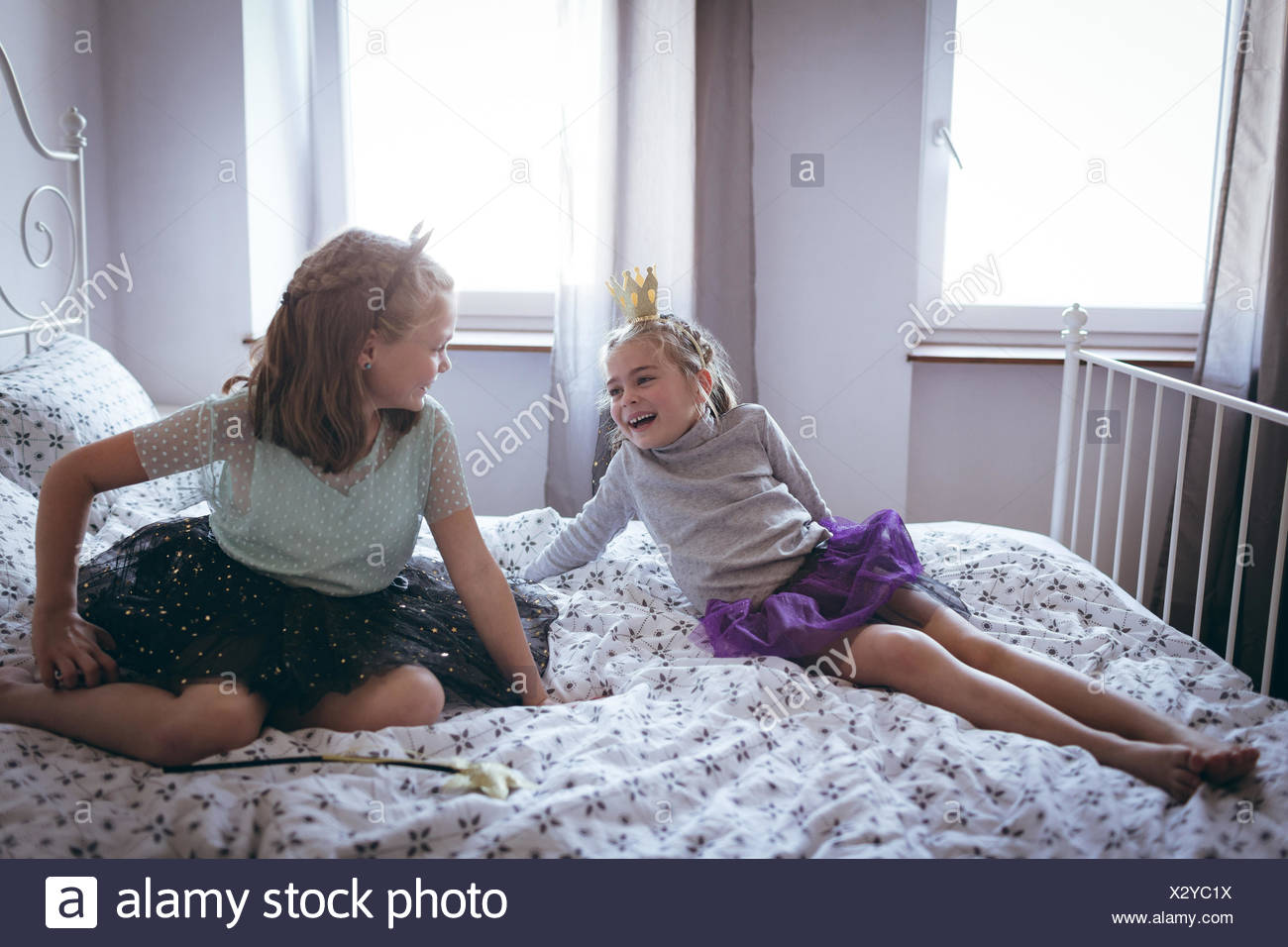 Sisters in costume having  fun on bed - Stock Image