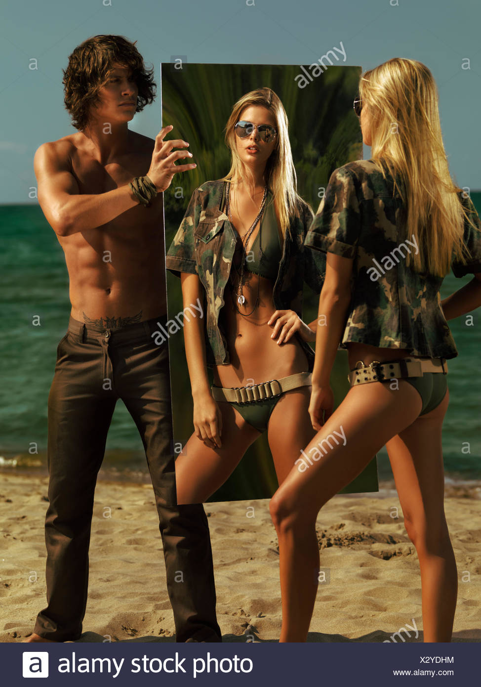 Woman wearing a military-style outfit watching herself in a mirror held by a man, on the beach, Toronto, Ontario Province - Stock Image