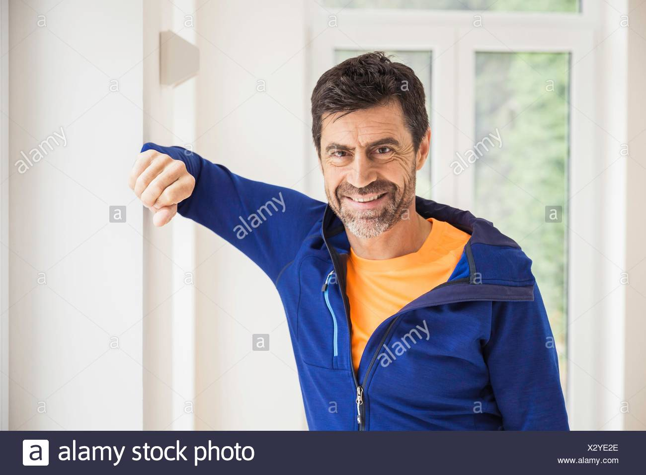 Portrait of mature man wearing tracksuit top at home - Stock Image