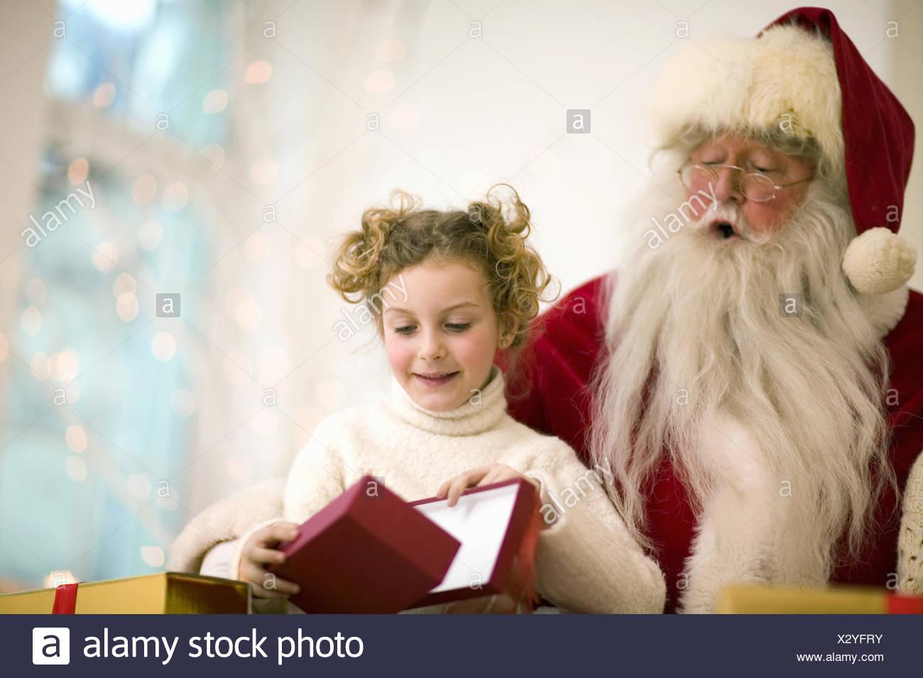 Santa Claus giving gift to young girl on Christmas - Stock Image