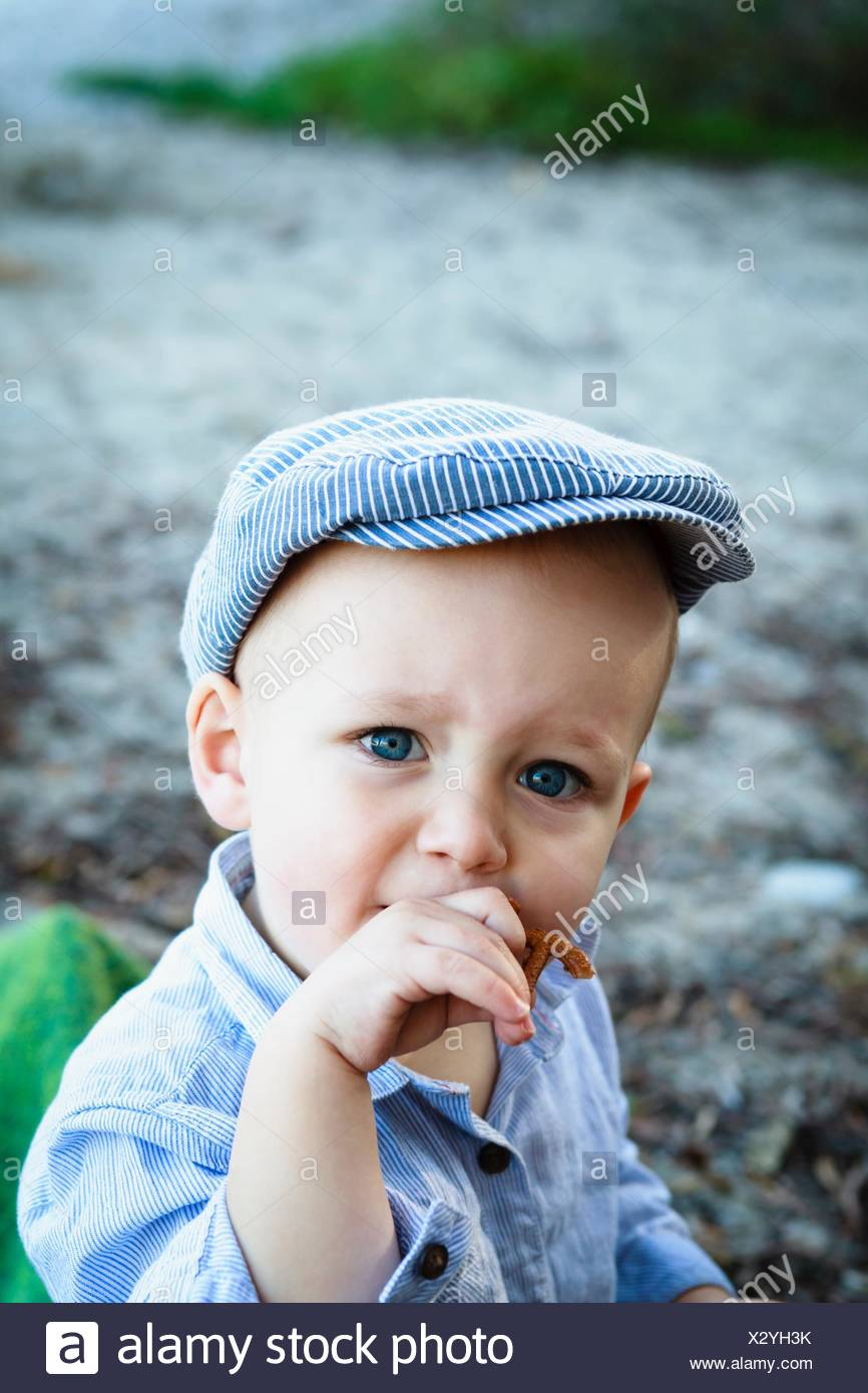 a6a813dd Portrait of young boy wearing flat cap, in rural setting - Stock Image