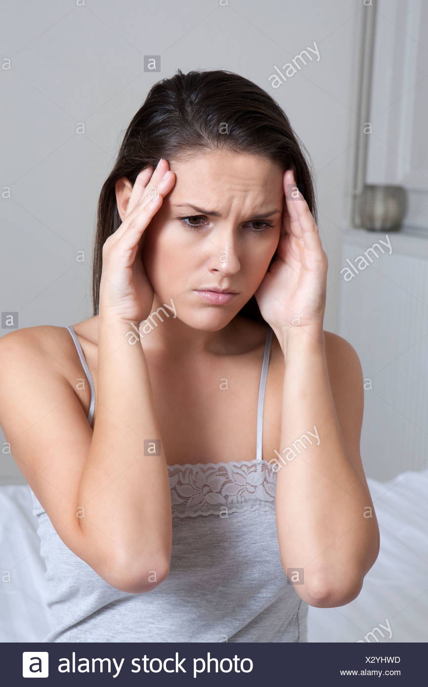 Woman rubbing her temples on bed - Stock Image