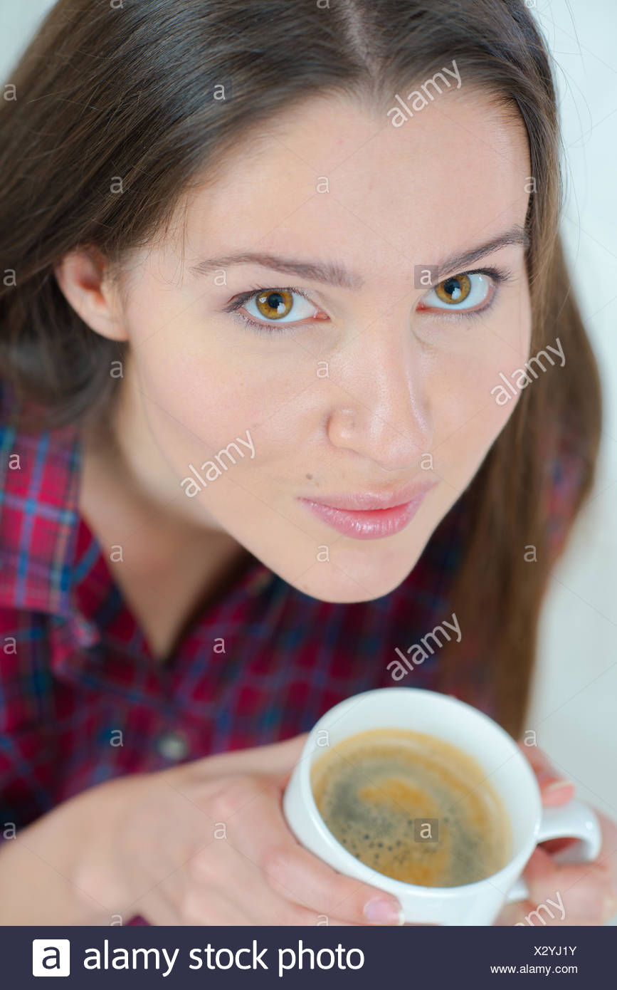 Woman drinking a cup of coffee on the sofa - Stock Image