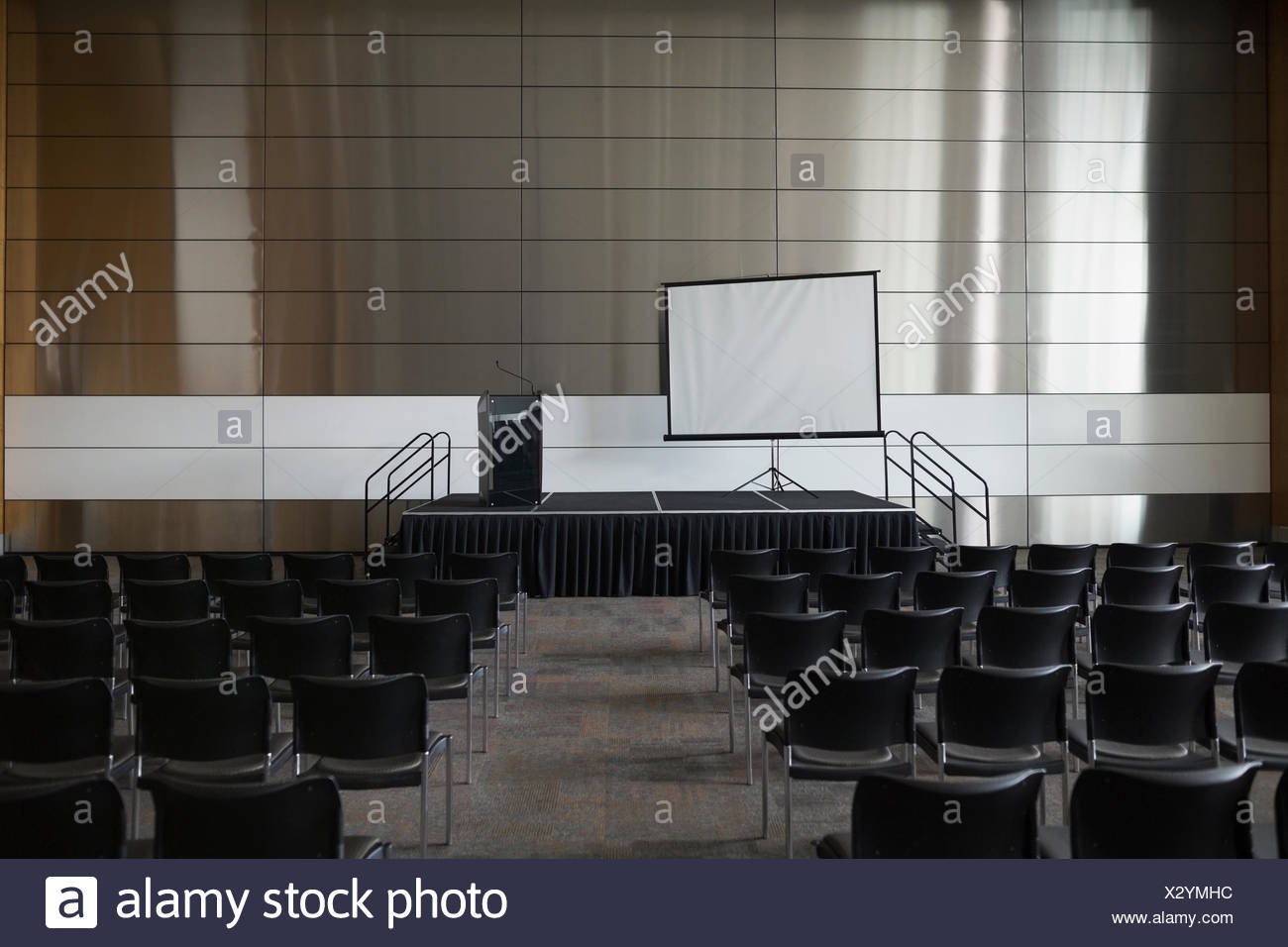Chairs and projection screen in empty auditorium - Stock Image