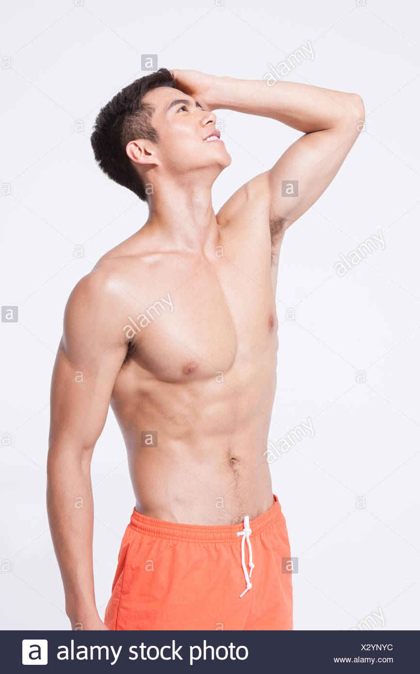 Muscular man in swimming pants putting his hand on his head