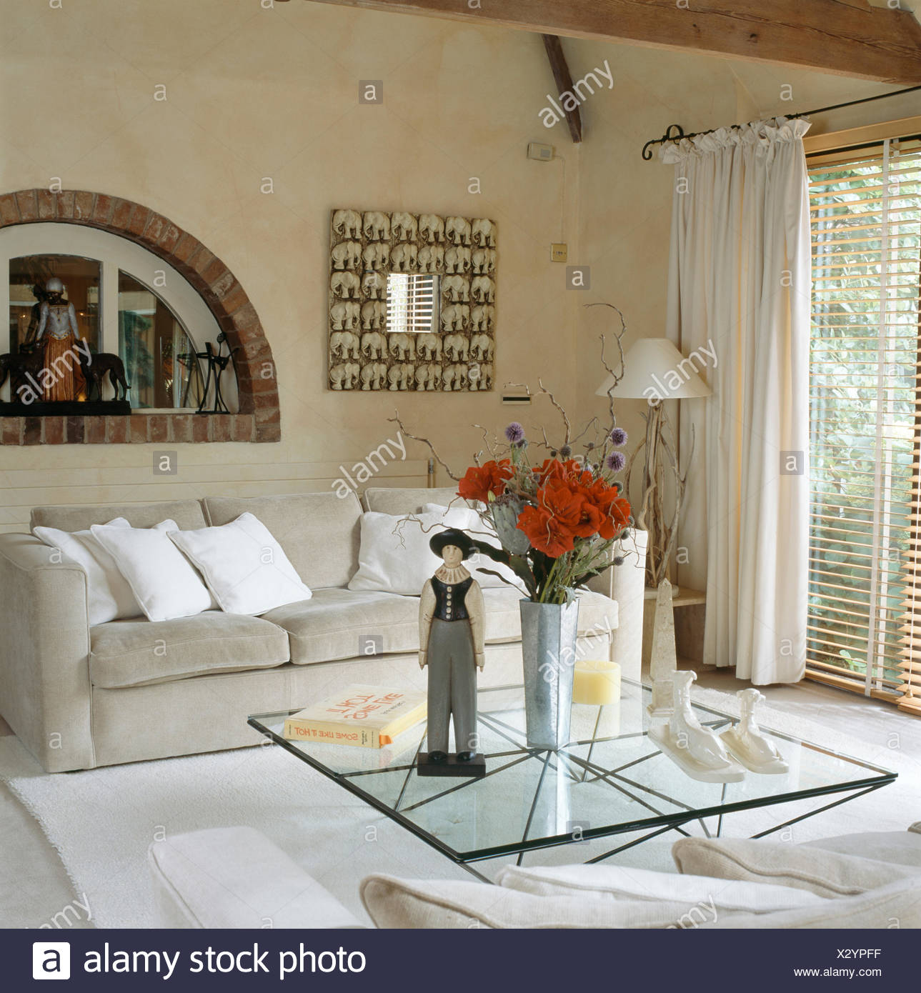 Wooden Figure On Glass Coffee Table In Modern Living Room With Arched Window Above Grey Sofa Stock Photo Alamy