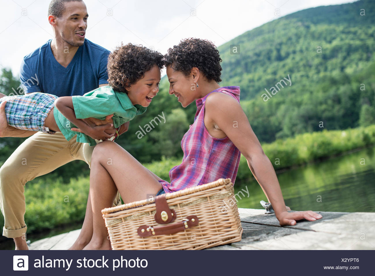 A family having a summer picnic at a lake. - Stock Image
