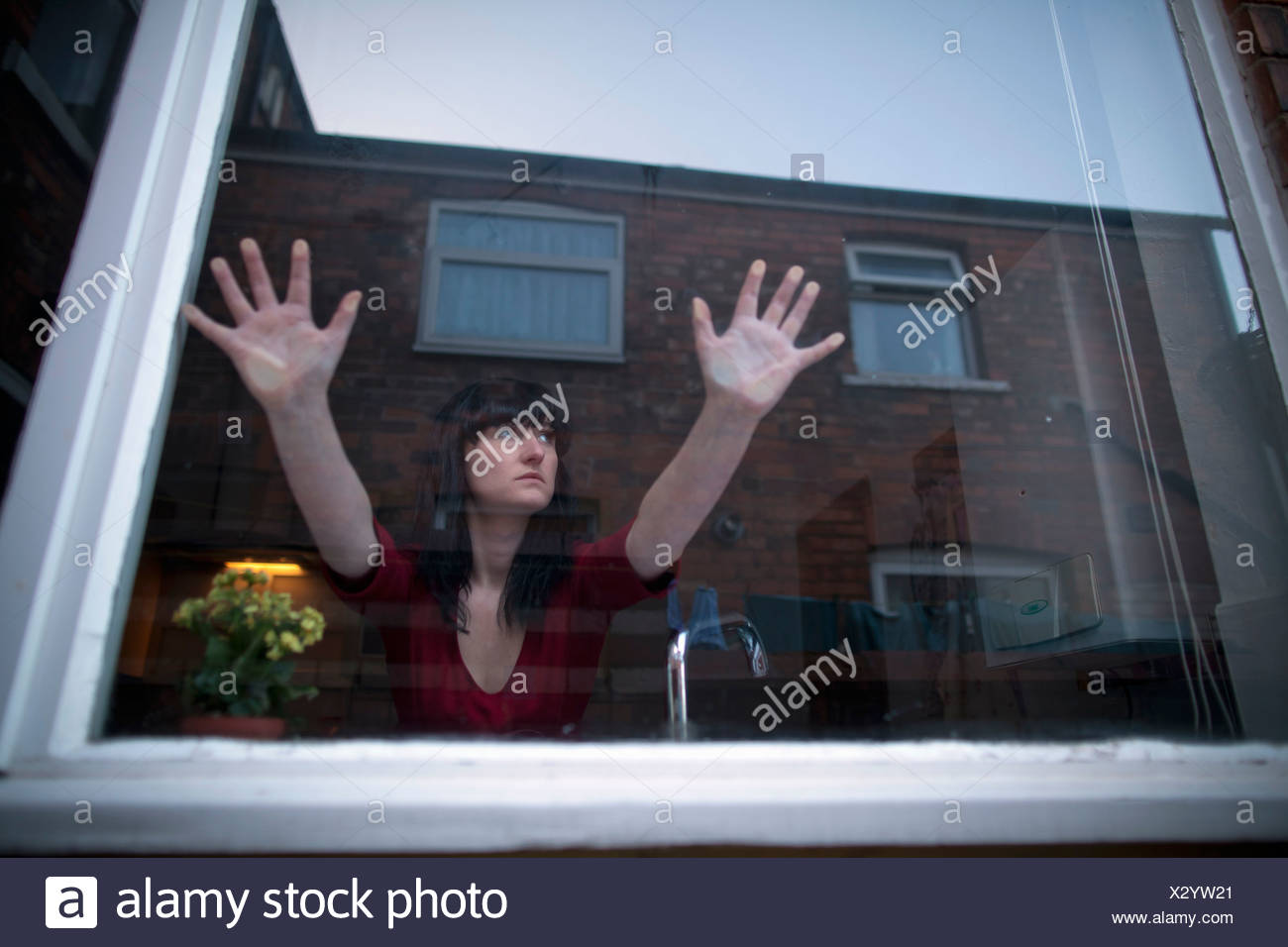 Woman in kitchen leaning on window Stock Photo