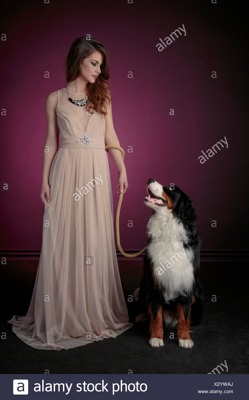 Young woman in evening gown with dog - Stock Image