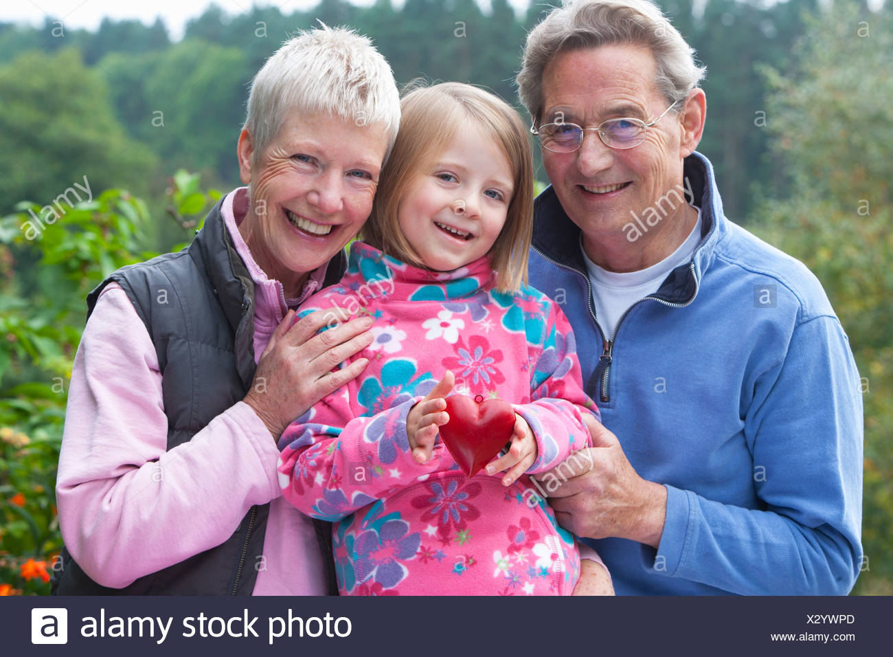 Portrait of smiling grandparents and granddaughter with heart-shape ornament in garden - Stock Image