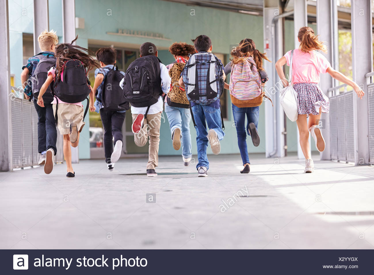 223ab43e2b4 Group of elementary school kids running at school, back view Stock ...