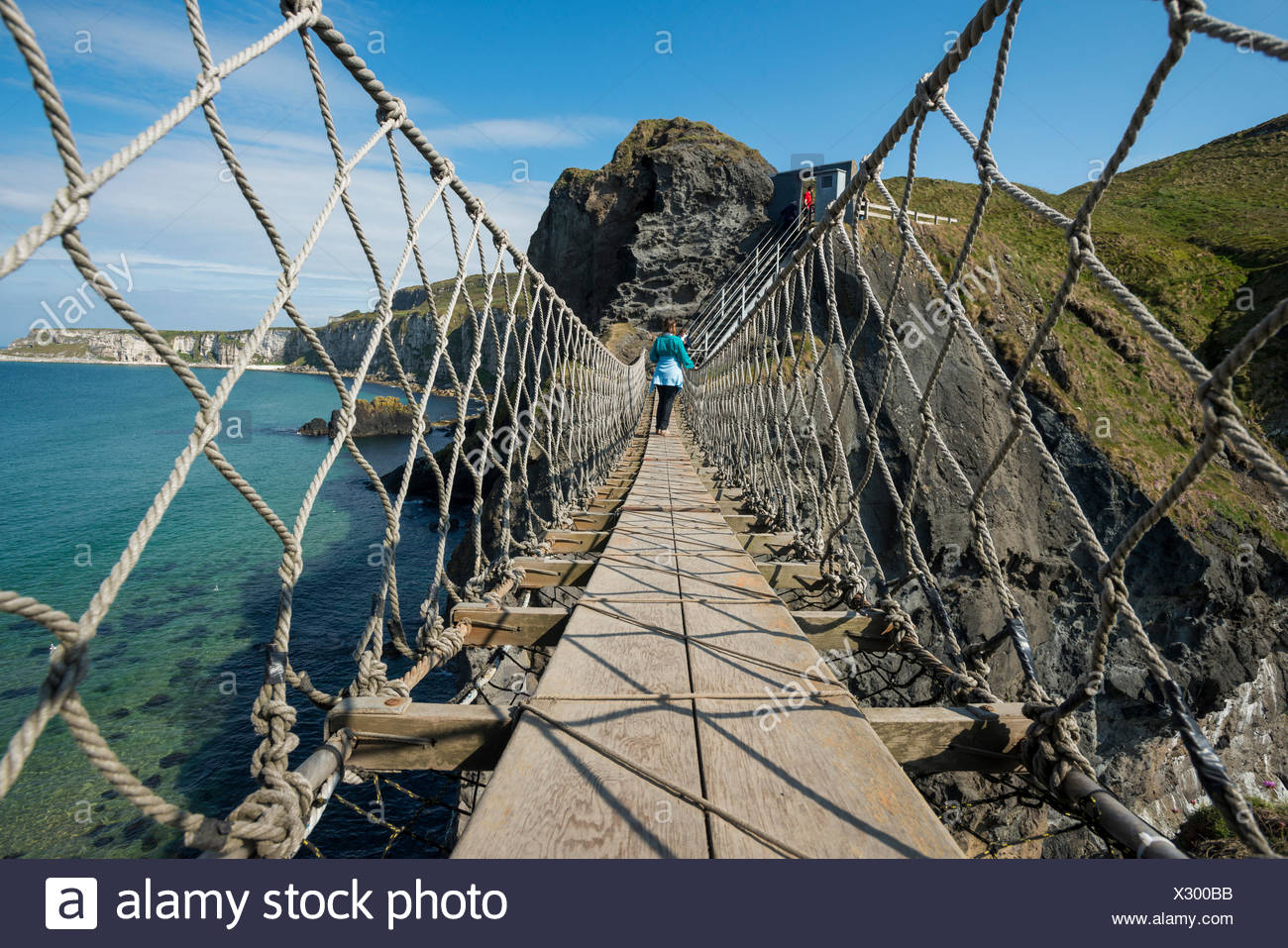 Carrick-a-Rede Bridge, woman crossing the suspension bridge, Moyle, Northern Ireland, United Kingdom, Europe - Stock Image