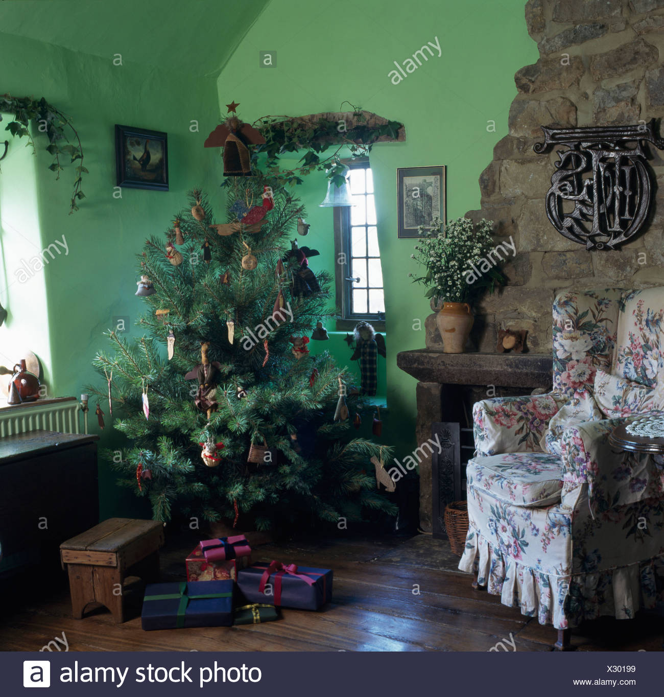 Christmas Tree In Corner Of Green Cottage Living Room With Wooden