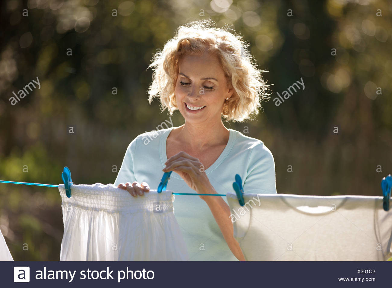 A mature woman pegging out washing on a washing line, smiling - Stock Image