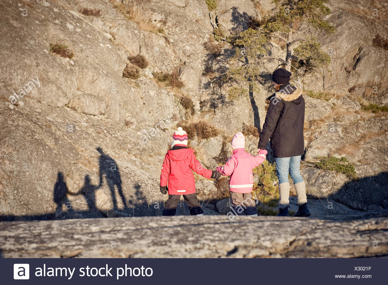 Sweden, Trosa, Mother with children looking at their shadows - Stock Image