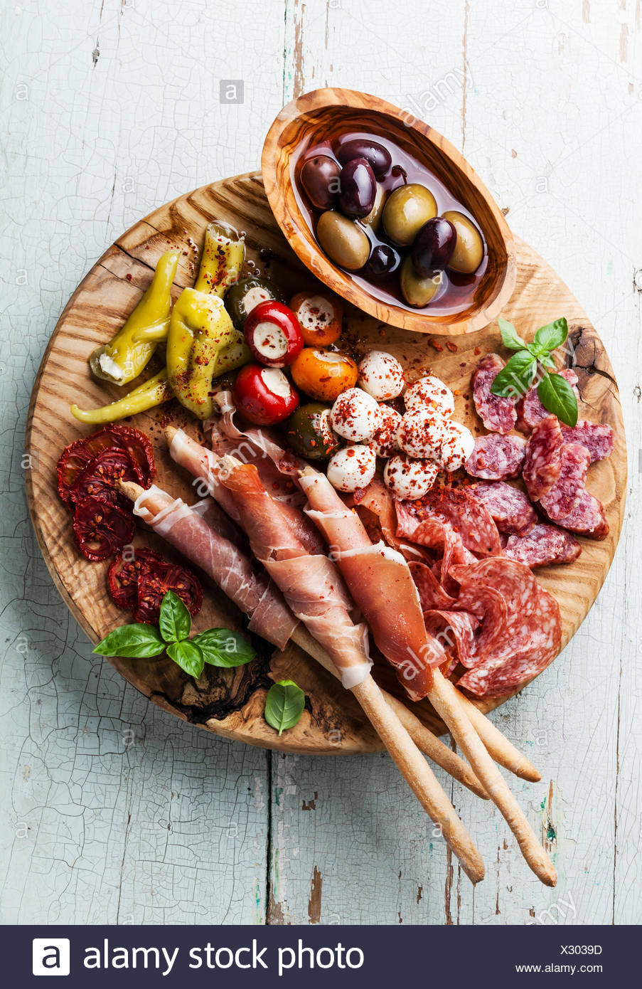 Antipasto Platter Cold meat plate with grissini bread sticks on blue wooden background - Stock Image