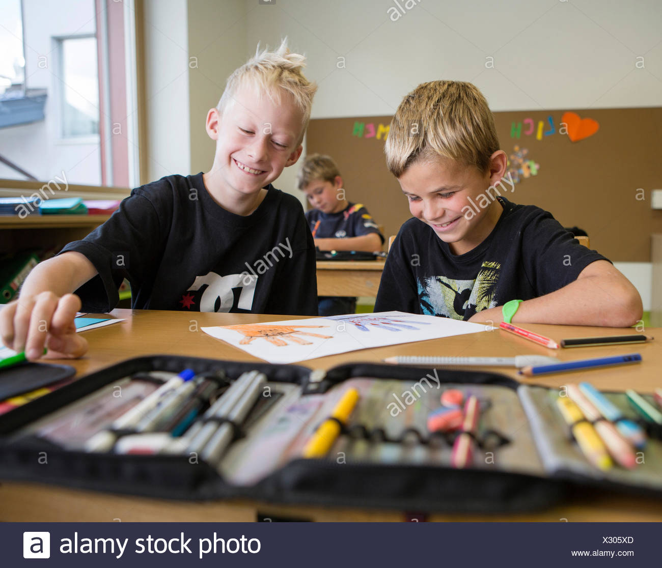 Smiling children sitting in a primary school class during a drawing lesson, Reith im Alpbachtal, Kufstein district, Tyrol - Stock Image