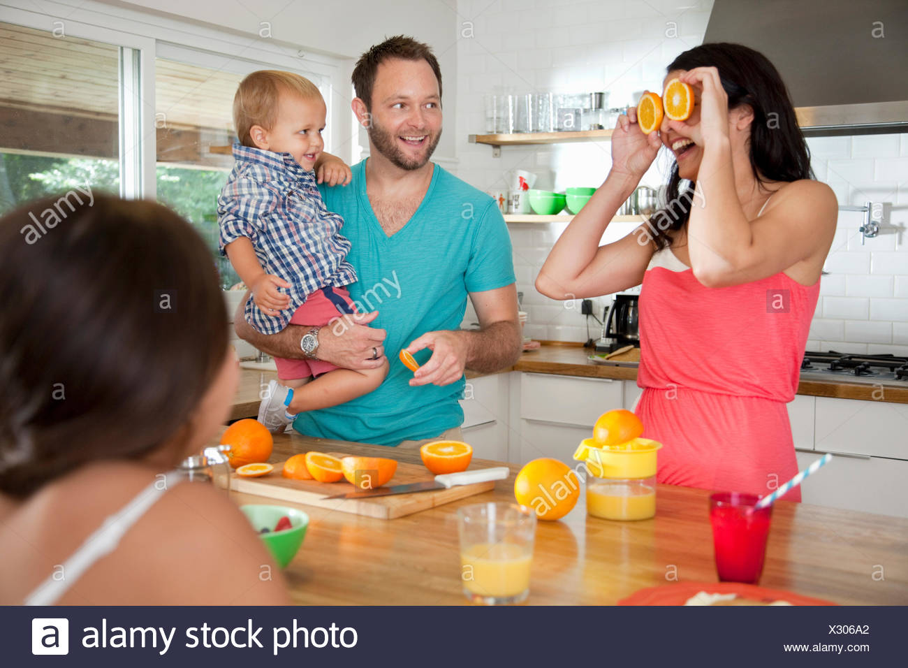 Mother making a face with oranges for her family at breakfast bar - Stock Image