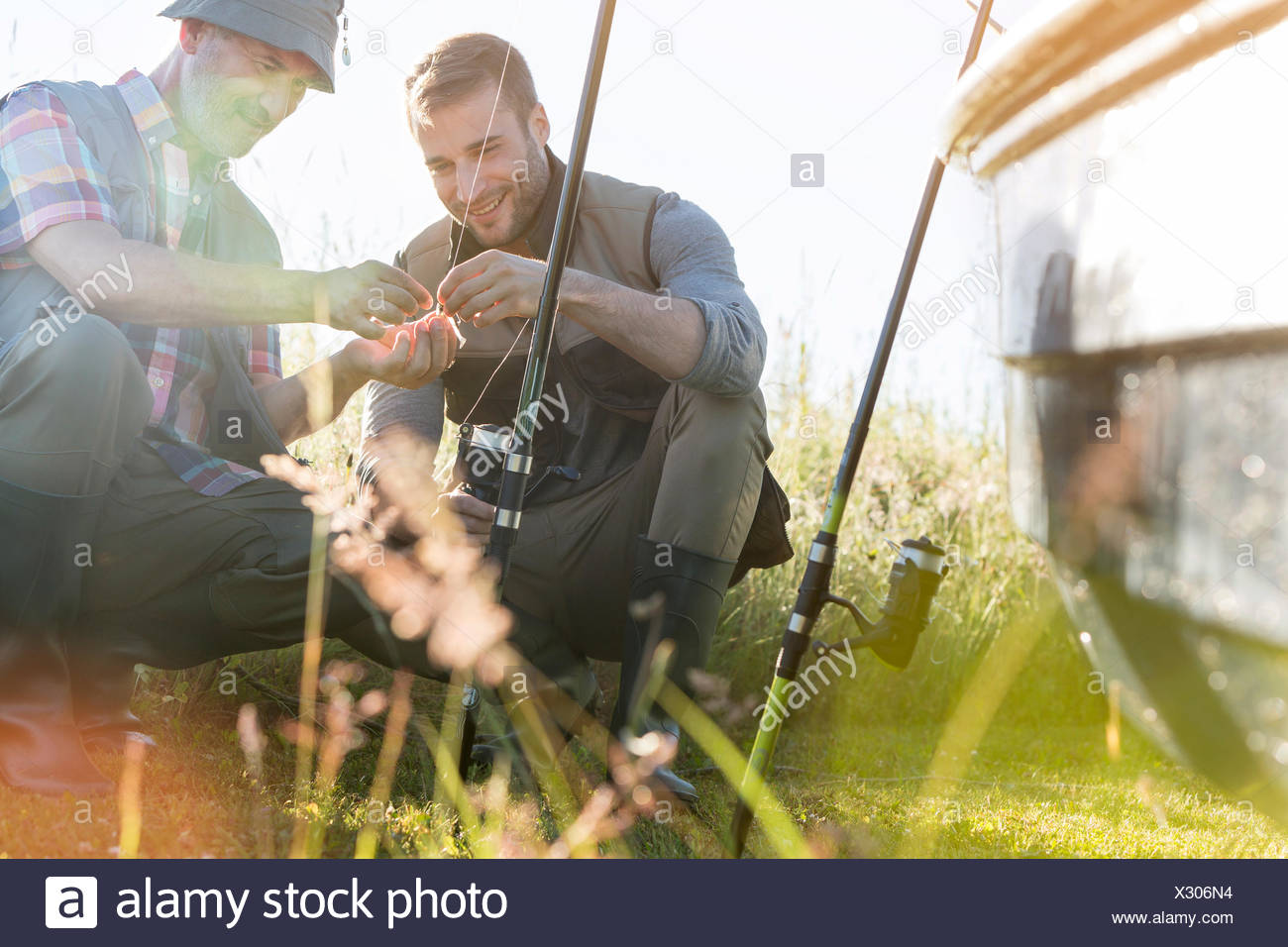Father and adult son preparing fishing lines - Stock Image