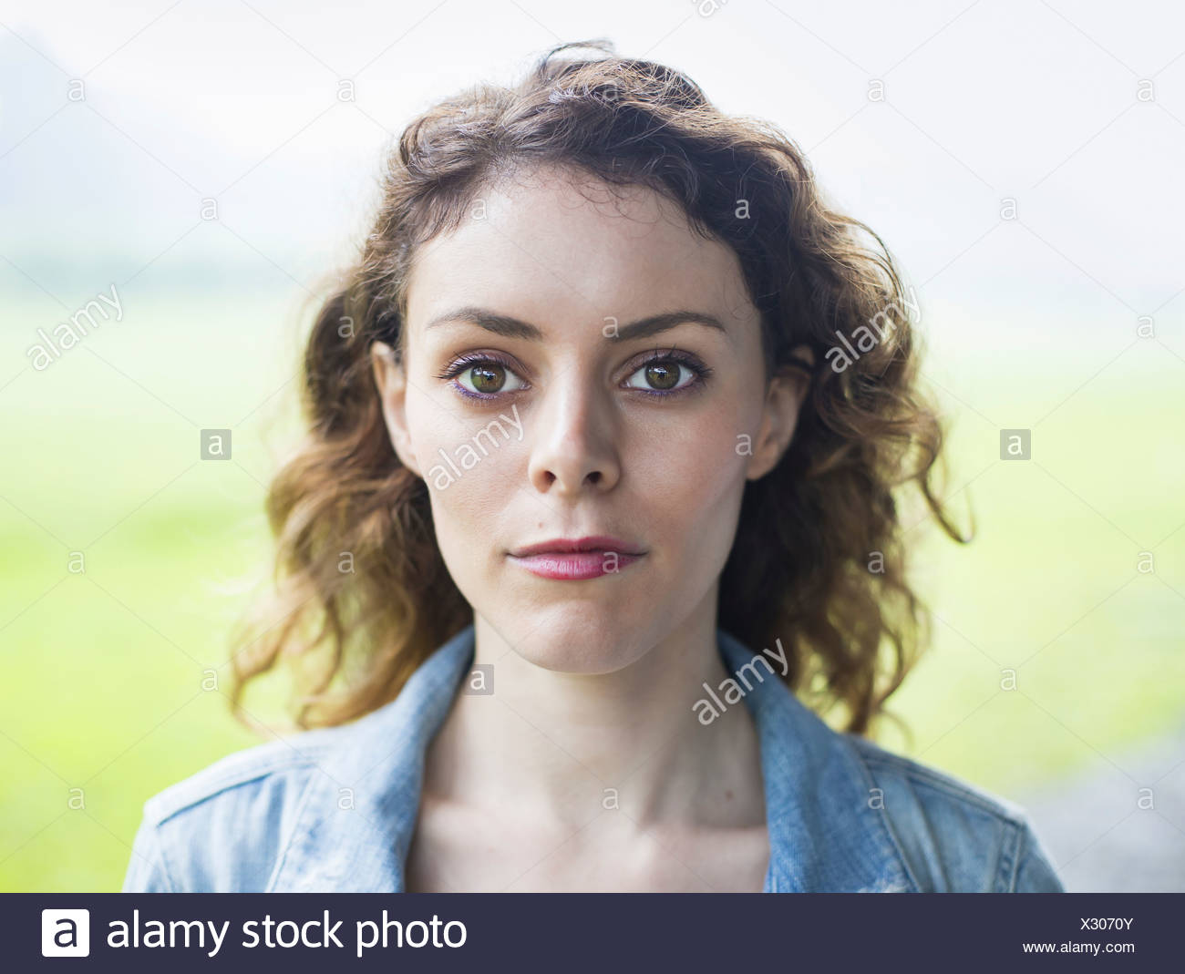 A young woman in a rural landscape with windblown curly hair. - Stock Image