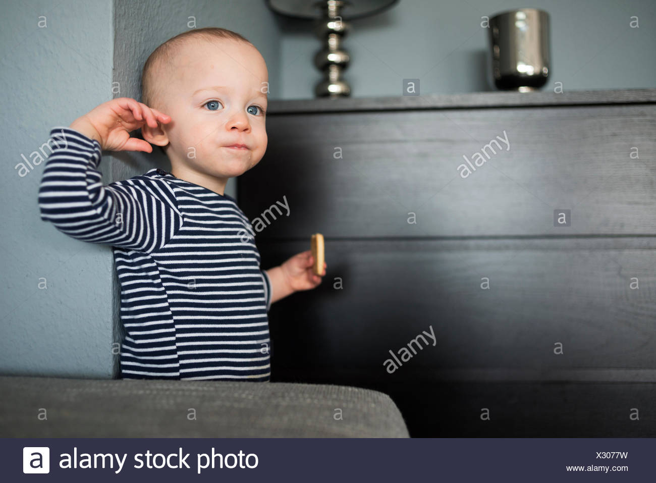 Baby boy eating biscuit in living room - Stock Image