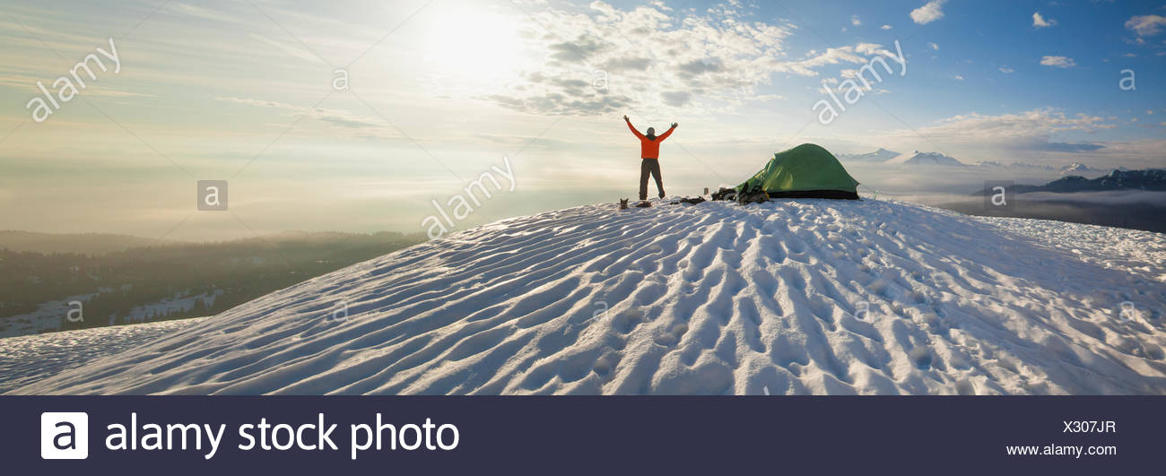 A climber poses beside his tent the morning after camping on the snow in the mountains. - Stock Image