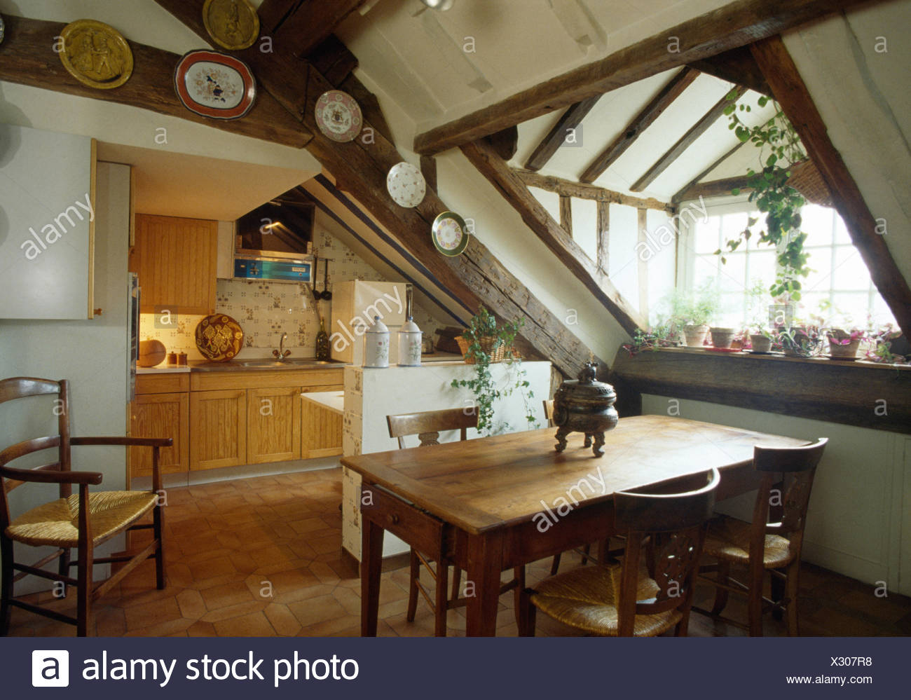 Simple pine table and chairs in attic kitchen dining room - Stock Image