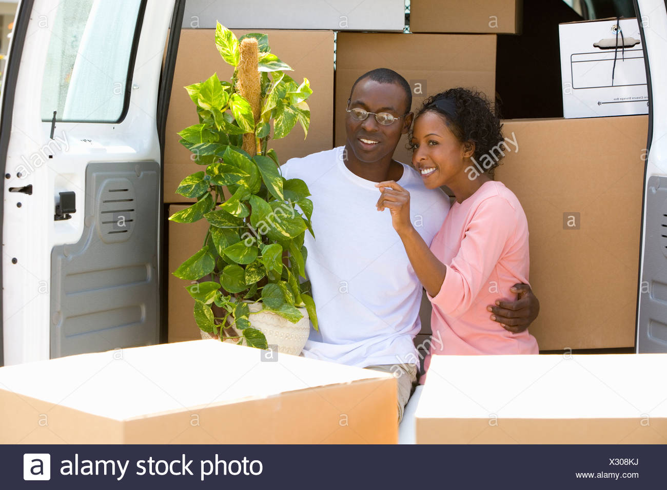 Couple unloading boxes from van Stock Photo