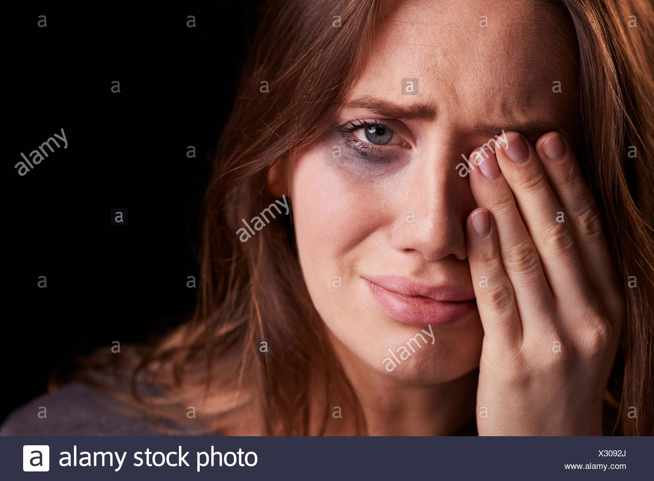 Studio Portrait Of Crying Young Woman With Smudged Eye Make Up - Stock Image