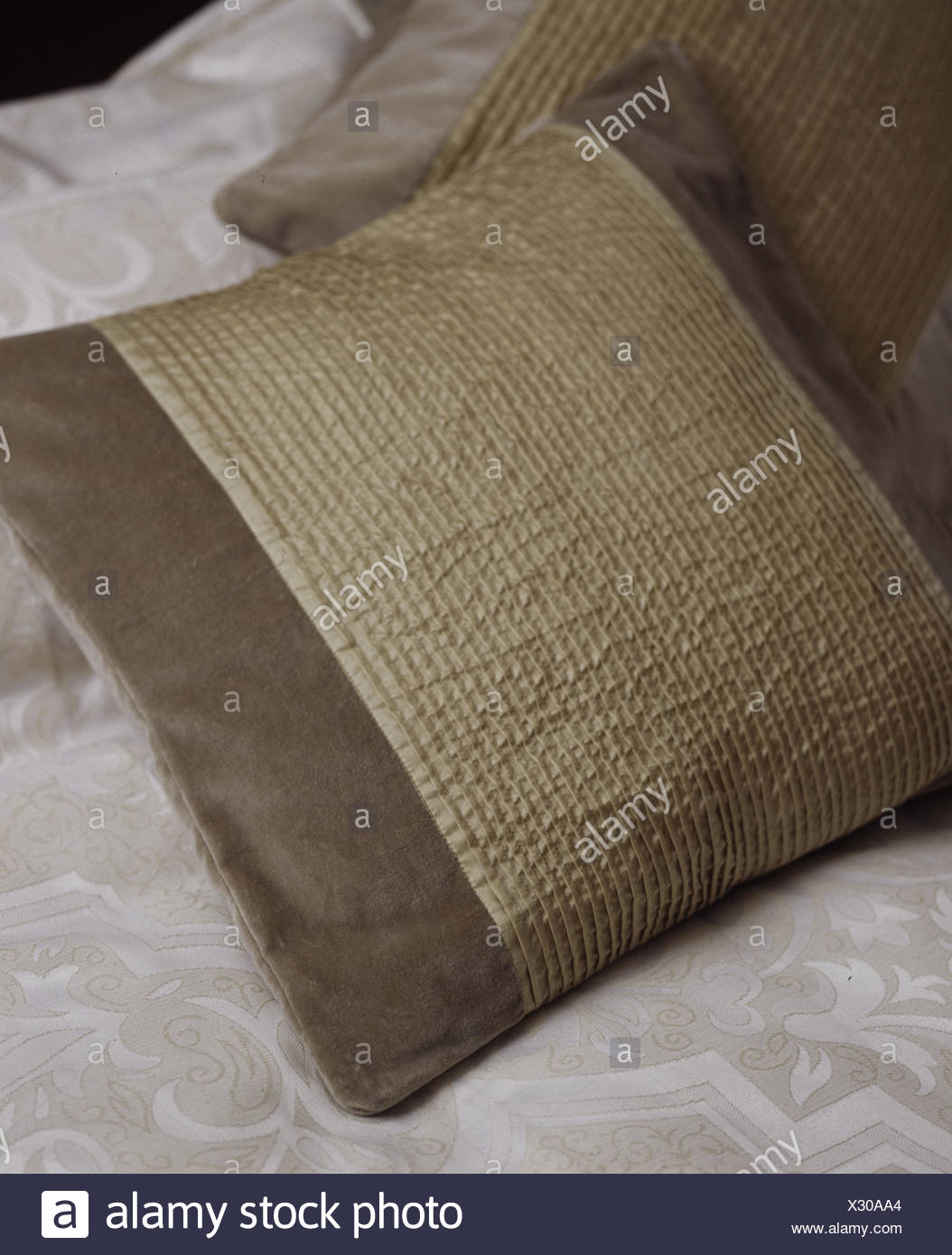 Closeup of brown and pleated cream silk cushion on bed - Stock Image
