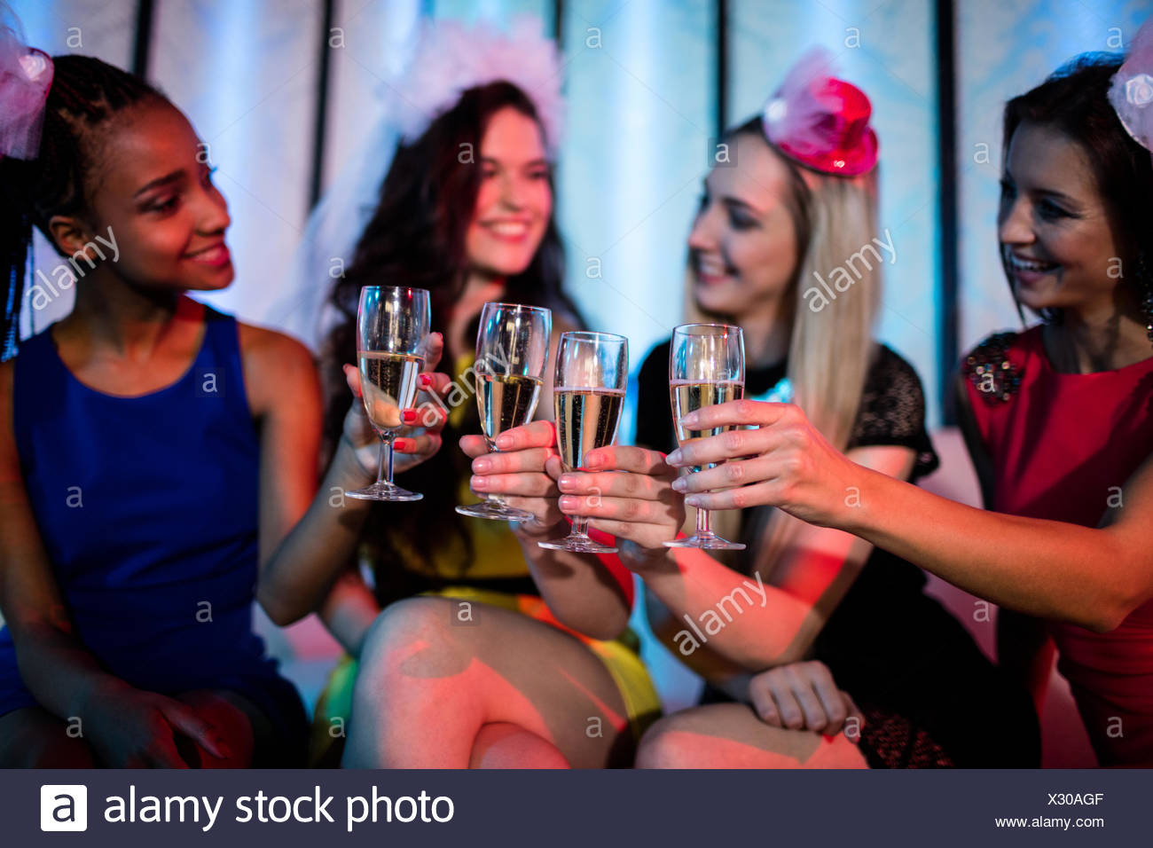 Group of smiling friend toasting glass of champagne - Stock Image