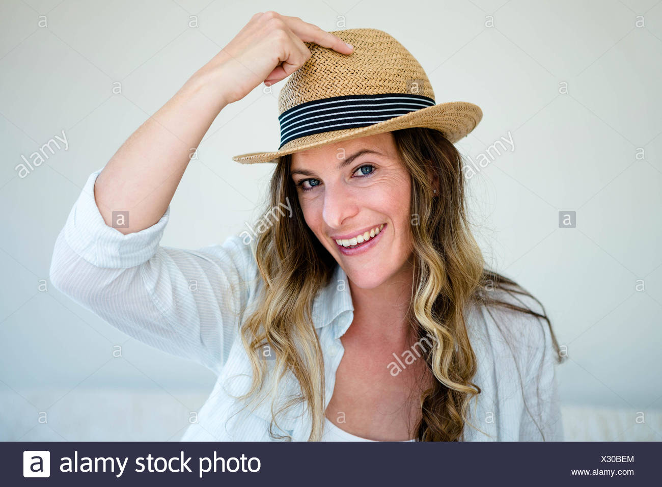 658a1afef6187 woman wearing a straw fedora smiling into the camera - Stock Image