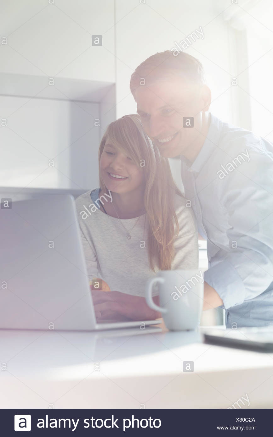 Father and daughter using laptop at home - Stock Image