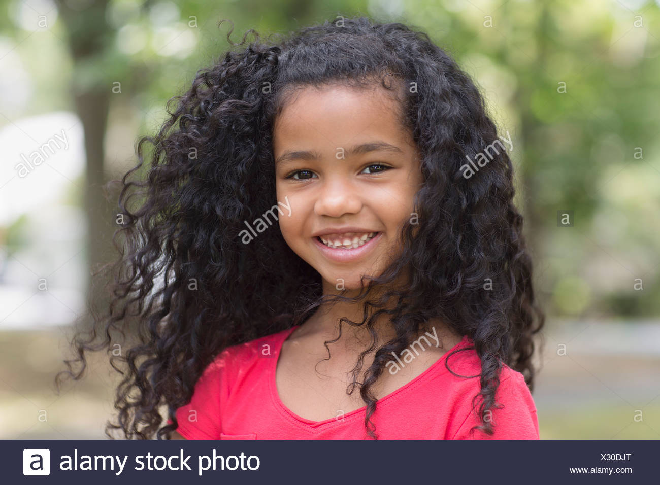 Close up portrait of young girl in park - Stock Image