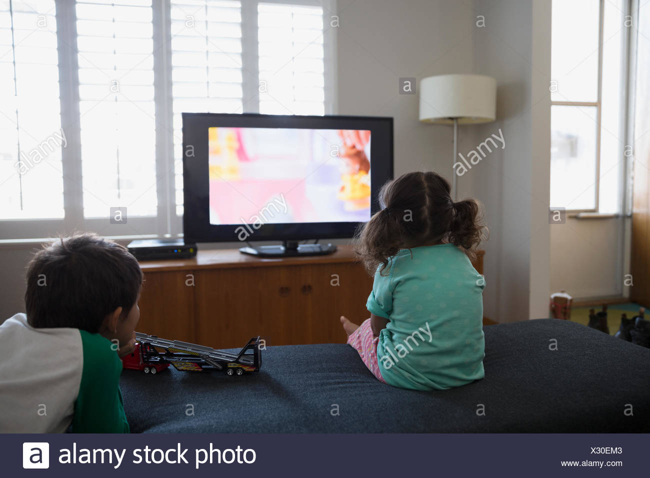 Brother and sister watching cartoons in living room - Stock Image