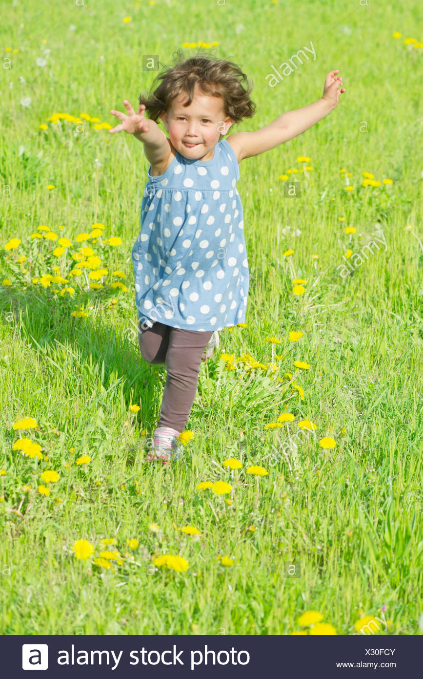 Little girl running in meadow - Stock Image