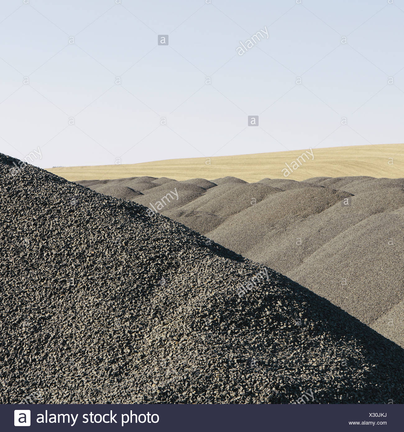 Gravel piles used for road maintenance and construction a row of heaps near Pullman Washington USA Stock Photo